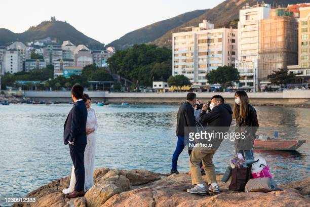 Hong Kong, China, 2 Jan 2021, A couple get their weeding pictorial done on rocks in Stanley Bay.