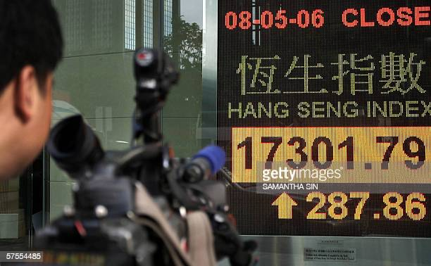 A cameraman records an electronic screen displaying the Hang Seng Index in Hong Kong 08 May 2006 Hong Kong share prices closed sharply higher with...