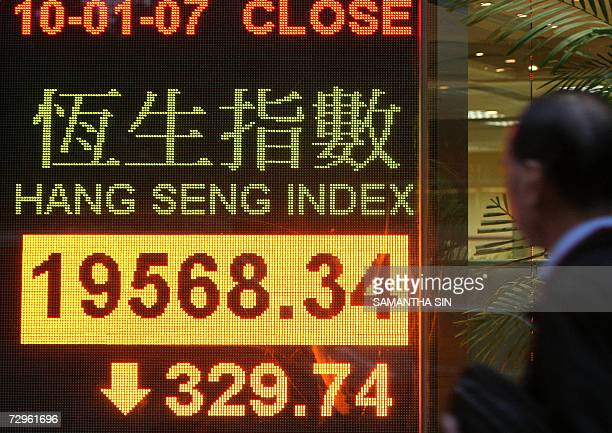 Man walk past a electric board displaying the Hong Kong share index, 10 January 2006. Share prices closed 1.66 percent lower in Hong Kong, extending...