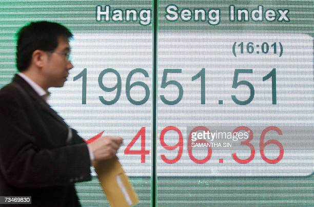 Man walks past a board displaying the Hang Seng Index outside a bank in Hong Kong, 28 February 2007. Hong Kong share prices closed sharply lower,...