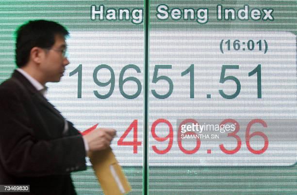Man walks past a board displaying the Hang Seng Index outside a bank in Hong Kong, 28 February 2007. Hong Kong share prices closed sharply lower,...