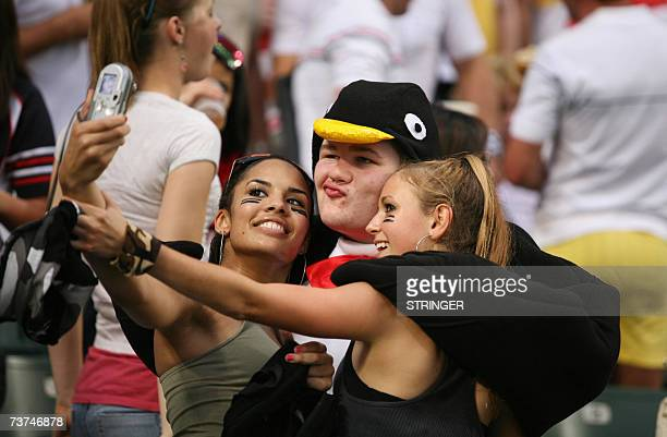 A supporter wearing a penguin costume poses for pictures with two women at the Cathay Pacific Credit Suisse Hong Kong Sevens in Hong Kong 30 March...