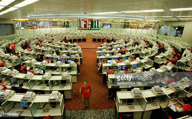 Trader walks along an aile at the Hong Kong stock exchange, 01 June 2006. The Hang Seng Index was down 16.69 points at 15,841.20, with the broader...