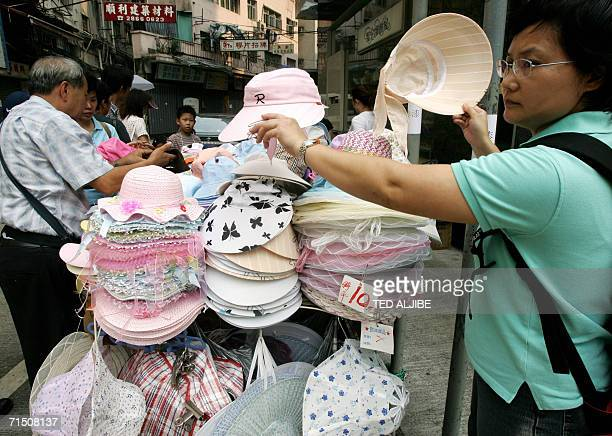 A woman buys a hat to shelter from the scorching heat of the sun in Hong Kong 24 July 2006 Temperatures reached 36 degrees celcius in Hong Kong AFP...