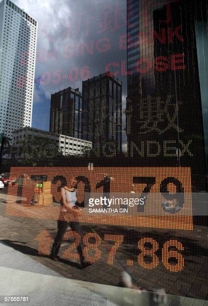 A woman is refected in a window behing which an electronic screen displays the Hang Seng Index in Hong Kong 08 May 2006 Hong Kong share prices closed...