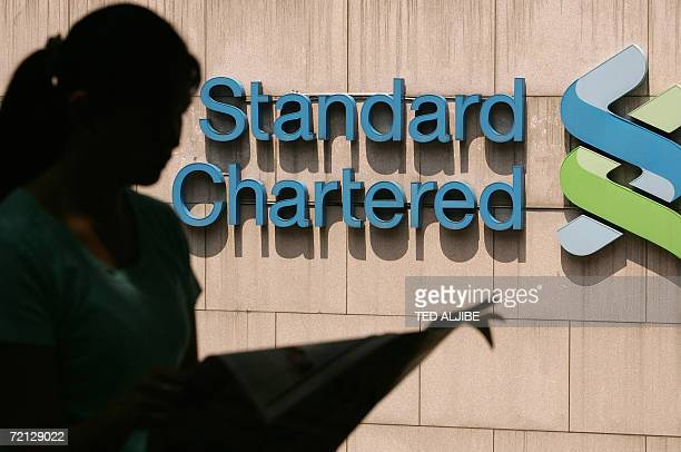 A woman reads a newspaper next to the logo of the Britishbased emerging markets bank Standard Chartered in Hong Kong 17 September 2006 AFP PHOTO/TED...