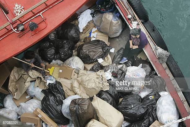 Bags of rubbish are taken away by sampan from the USS Blue Ridge flagship of the seventh fleet command in Hong Kong 16 February 2006 The ship is on a...