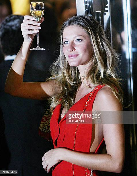 Brazilian model Gisele Bundchen raises a glass of Champagne after the ribbon cutting ceremony during the grand opening ceremony of the Louis Vuitton...
