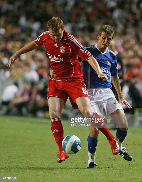 British premiership football club Liverpool's John Arne Riise runs past Portsmouth player Martin Crainie during the Barclays Asia Trophy Final in...