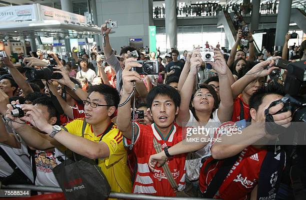 Fans of English football team Liverpool cheer and take pictures as the team arrives at Chek Lap Kok Airport in Hong Kong 22 July 2007 Liverpool will...