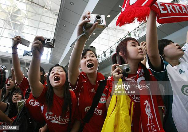 Fans take pictures of English football team Liverpool as they pose for pictures after the team arrived at Chek Lap Kok Airport in Hong Kong 22 July...