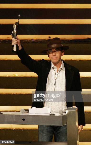 Hong Kong actor Anthony Wong raises the trophy after winning the Best Supporting Actor for his film initial D at the 25th Hong Kong film awards AFP...