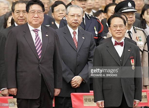 Hong Kong Chief Executive Donald Tsang stands at attention with Hong Kong's Secretary for Housing Planning and Lands Michael Suen and Gao Siren head...