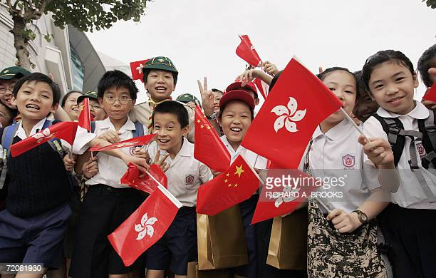 Local schoolchildren wave Chinese and Hong Kong flags at an official flag raising ceremony outside the Hong Kong Convention and Exhibition Centre 01...