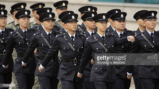 Members of the Hong Kong police march in formation ahead of an official flag raising ceremony outside the Hong Kong Convention and Exhibition Centre...