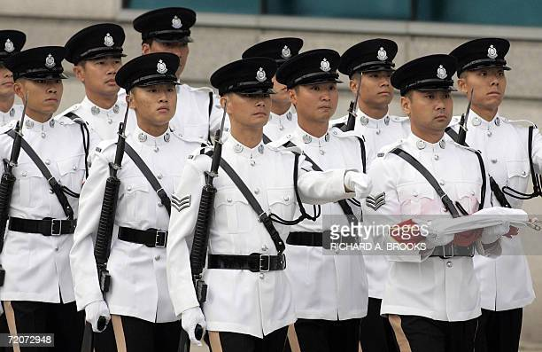 Members of the Hong Kong police march in formation carrying the flags ahead of an official flag raising ceremony outside the Hong Kong Convention and...