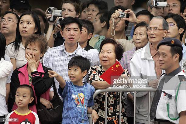 Members of the public look up at a large video screen as they watch an official flag raising ceremony outside the Hong Kong Convention and Exhibition...