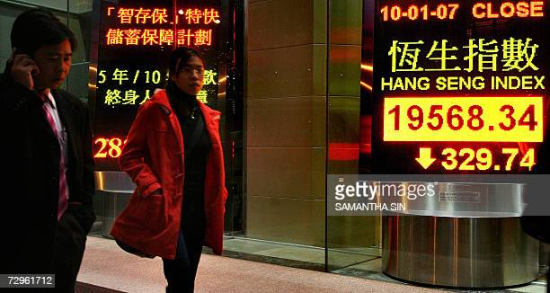 Pedestrians walk by an electric board displaying the Hong Kong share index 10 January 2006 Share prices closed 166 percent lower in Hong Kong...