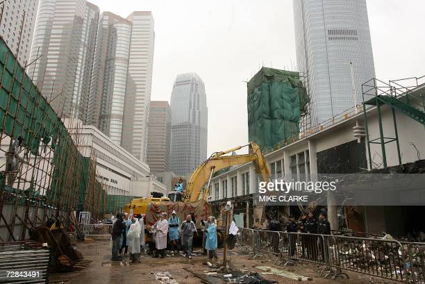 Protesters mill around the construction site of the old ferry pier in Hong Kong 13 December 2006 after they broke in in a bid to halt a demolition of...