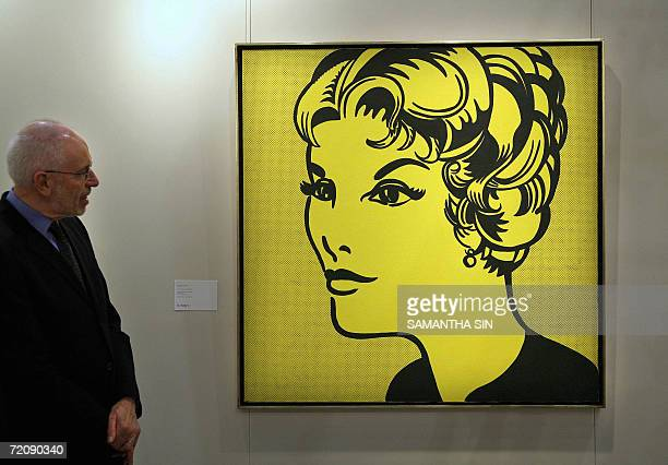 Sotheby's senior vice president John L Tancock looks at one of contemporary paintings 'Head Yellow and Black' by Roy Lichtenstein on display at a...