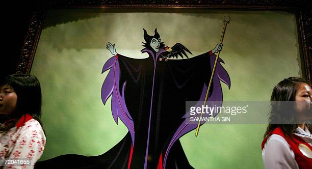 Staff stand next to a portrait of Disney character Cruella De Vil during a Halloween celebration press preview in Hong Kong 29 September 2006 The...