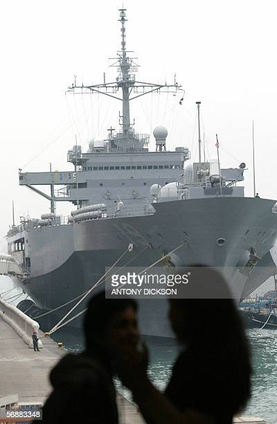 Two pedestrians stop to look at the USS Blue Ridge docked in the harbour in Hong Kong, 19 February 2006. The USS Blue Ridge, which has been...