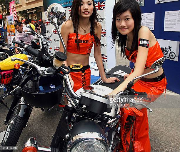 Two promotional girls pose next to a Britishmade Triumph motorcycle on display at the Classic AutoCycle Museum show in Hong Kong 05 November 2006 The...