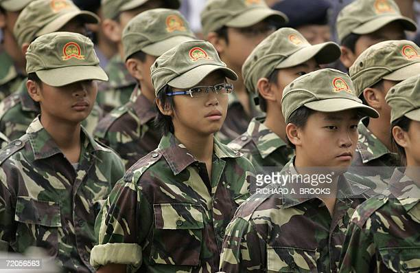 Young people in uniform wait in formation ahead of an official ceremony outside the Hong Kong Convention and Exhibition Centre 01 October 2006 as the...
