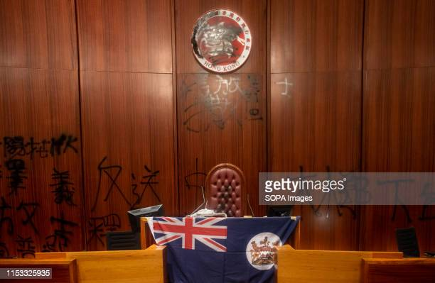 Hong Kong colonial flag and a defaced Hong Kong emblem during the demonstration Hundreds of antigovernment protesters stormed into the legislative...