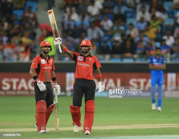 Hong Kong cricketer Nizakat Khan celebrates 50 runs as captain Anshuman Rath looks on during the 4th cricket match of Asia Cup 2018 between India and...