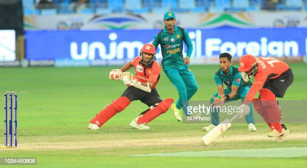Hong Kong cricketers Ehsan Nawaz and Nadeem Ahmed tries to make the crease to complete a run at the same end as Pakistan crcicketer Hasan Ali tries...