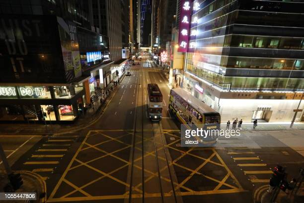 Hong Kong crosswalk in business financial district downtown tramway and bus are crossing street
