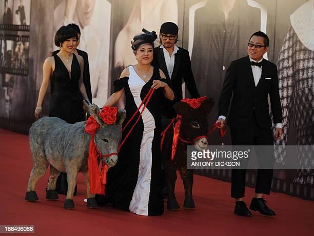 Hong Kong director Pang Ho Cheung and Hong Kong actress Susan Shaw pose with toy donkeys for photographers on the red carpet during the 32nd Hong...