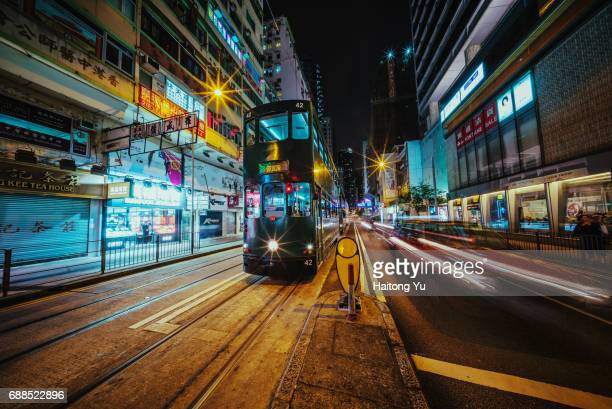 hong kong. double-decker tram bus at night - wanchai stock photos and pictures