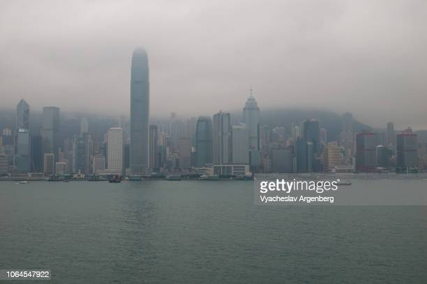 hong kong dramatic skyline, rain, fog and high humidity in victoria harbor - argenberg stock pictures, royalty-free photos & images