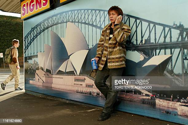 Hong Kong exchange student Alex Lee talks on his Telstra mobile phone beside a poster featuring the Sydney Opera House and the Sydney Harbour Bridge...