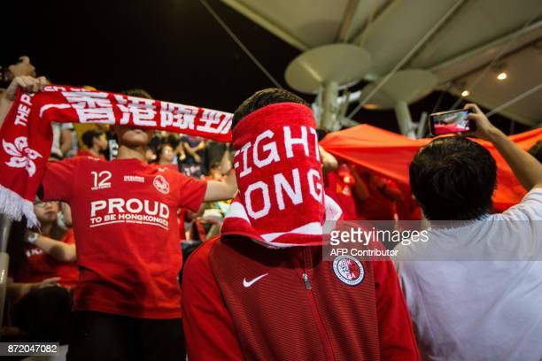A Hong Kong fan covers his face during the Chinese national anthem before an international friendly football match between Hong Kong and Bahrain at...