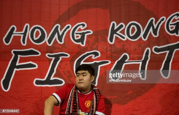 A Hong Kong fan sits in front of a flag before an international friendly football match between Hong Kong and Bahrain at Mong Kok Stadium in Hong...