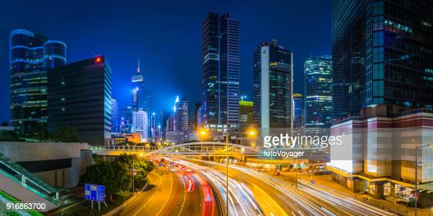 hong kong futuristic highrises highways traffic skyscrapers neon night panorama - wanchai stock photos and pictures