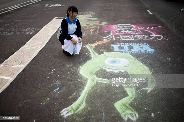 Hong Kong girl looks at Mike Wazowski of Monsters Inc movie painting on the street at Admiralty Camp on November 20 2014 in Hong Kong Hong Kong In a...