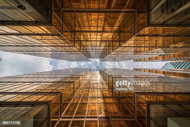 hong kong. gold colored glass curtain wall of malls at china hong kong city - fluchtpunkt stock-fotos und bilder