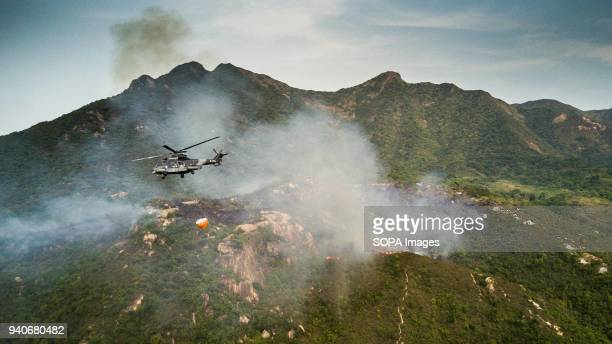 A Hong Kong government flying services Eurocopter AS332 Super Puma helicopter seen trying to extinguish a forest fire during a fire fighting mission...