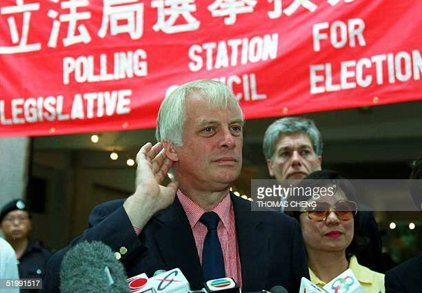 Hong Kong Governor Chris Patten listens to reporters questions after visiting a polling station in the New Territories area of Hong Kong 17 September...