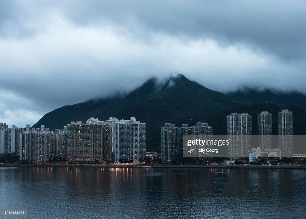 Hong Kong high-rise skyline with mountains and clouds : Stock Photo