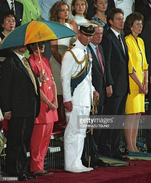 Britain's Prince Charles watches the British Military Farewell Ceremony at the HMS Tamar military base in Hong Kong 30 June 1997 marking the end of...