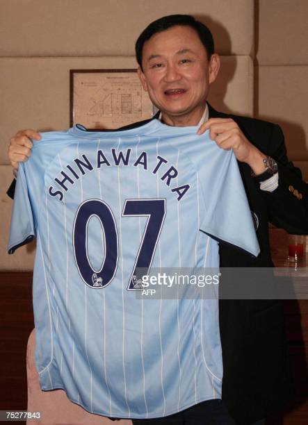 Ousted Thailand Prime Minister Thaksin Shinawatra shows a jersey of Manchester City English Premiership club during interview with the Thai press at...