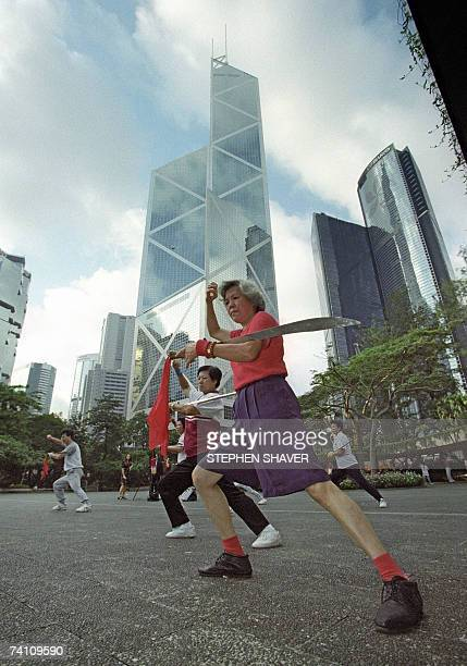 People practice different variations of the martial art of 'tai chi' in the Central district of Hong Kong 27 June 1997 three days before the end of...