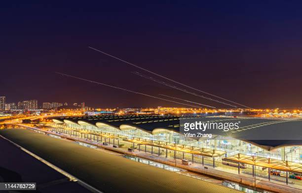 hong kong international airport terminal with light trails of planes at night - lantau stock pictures, royalty-free photos & images