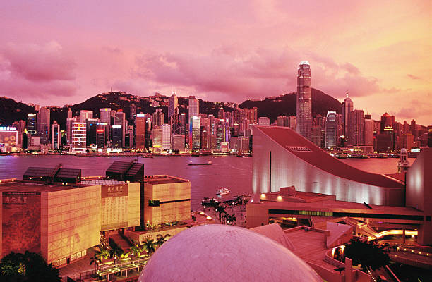 Hong Kong Island skyline, Victoria Harbour, Museum of Art, Space Museum and Cultural Centre in Tsim Sha Tsui at sunset.