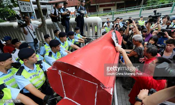 Hong Kong lawmaker Leung Kwokhung burns a letter he was unable to deliver to Chinese President Hu Jintao as he stands in front of a 'mock coffin' Hu...